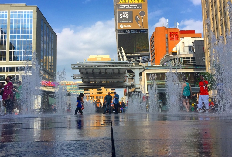 Try to dance without getting wet! Fountain Day at Dundas Square in Toronto.